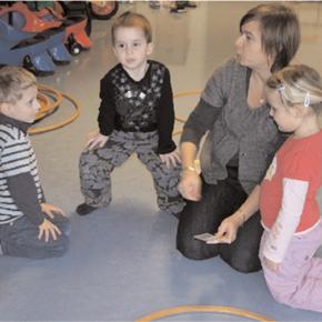 3 Kinder und eine Betreuerin am Boden im Kreis sitzend