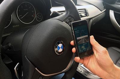 Hand hält Mobiltelefon vor Lenkrad im Auto