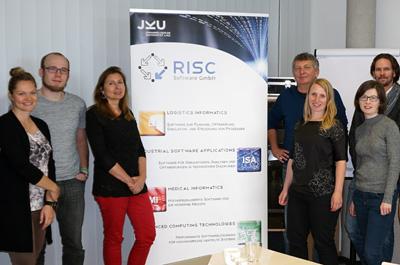 7 Personen stehend neben Roll-up der RISC Software GmbH