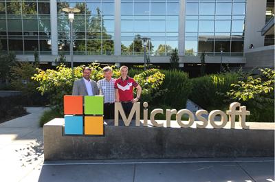 3 Personen stehend vor Haus mit Glasfront, hinter einer Skulptur Microsoft Logo