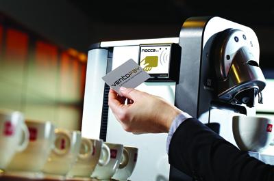 Hand hält Chipkarte vor Kaffemaschinen Automatenmodul