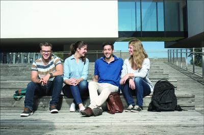 4 Personen sitzend im Innenhof der FH Oberösterreich Campus Hagenberg und in Kamera schauend