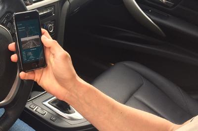 Person sitzt im Auto auf der Fahrerseite und hält Smartphone