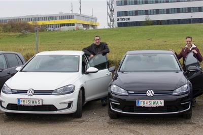 2 Personen stehend neben ihren beiden Elektro-Autos