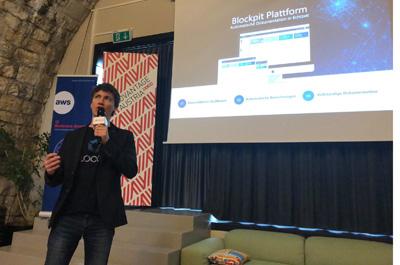Blockpit CEO Florian Wimmer präsentiert die Firma, er steht vor einer Leinwand und hält ein Mikrofon in der Hand