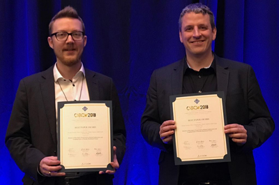 2 Männer stehen und halten ihre Best Paper Awards Richtung Kamera