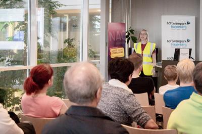 1 Person steht und präsentiert ein Thema, davor sitzen viele Zuseher, die dem Vortrag lauschen