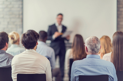 Personen sitzen in einem Schulungsraum, Rücken zu Kamera gedreht, Vortragender steht ganz vorne