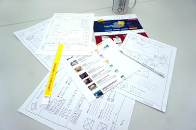 Zettel, Stift, Notizen und Kaffeebecher sind auf Tisch platziert