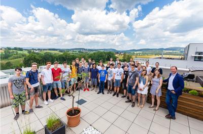 Eine Schulklasse steht auf der Dachterasse, auf dem Foto sieht man den Ausblick auf den Softwarepark Hagenberg.