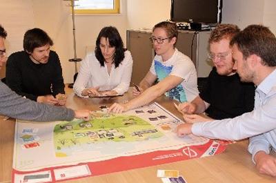 6 Personen sitzen bei Tisch und spielen Simulationsspiel Zero Downtime in Action