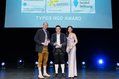 3 Personen stehen auf Bühne vor Leinwand und halten den Award in Händen