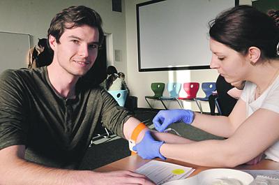 einem Mann wird von einer Frau Blut zur Stammzellentypisierung abgenommen, er blickt lächelnd in Kamera