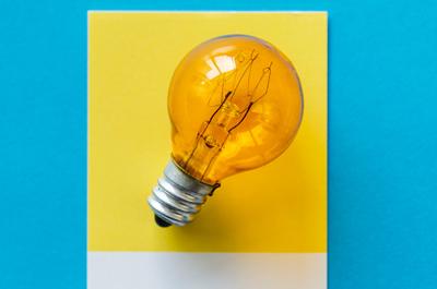 Image-Bild gelbe Glühbirne auf gelbem Zettel auf blauem Hintergrund