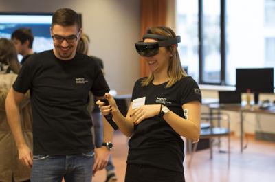 2 Personen stehen, 1 davon hat Virtual Reality Brille im Gesicht