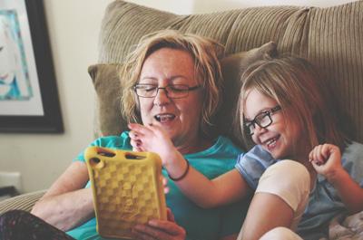 Mutter und Tochter sitzen auf Sofa und spielen auf einem Tablet